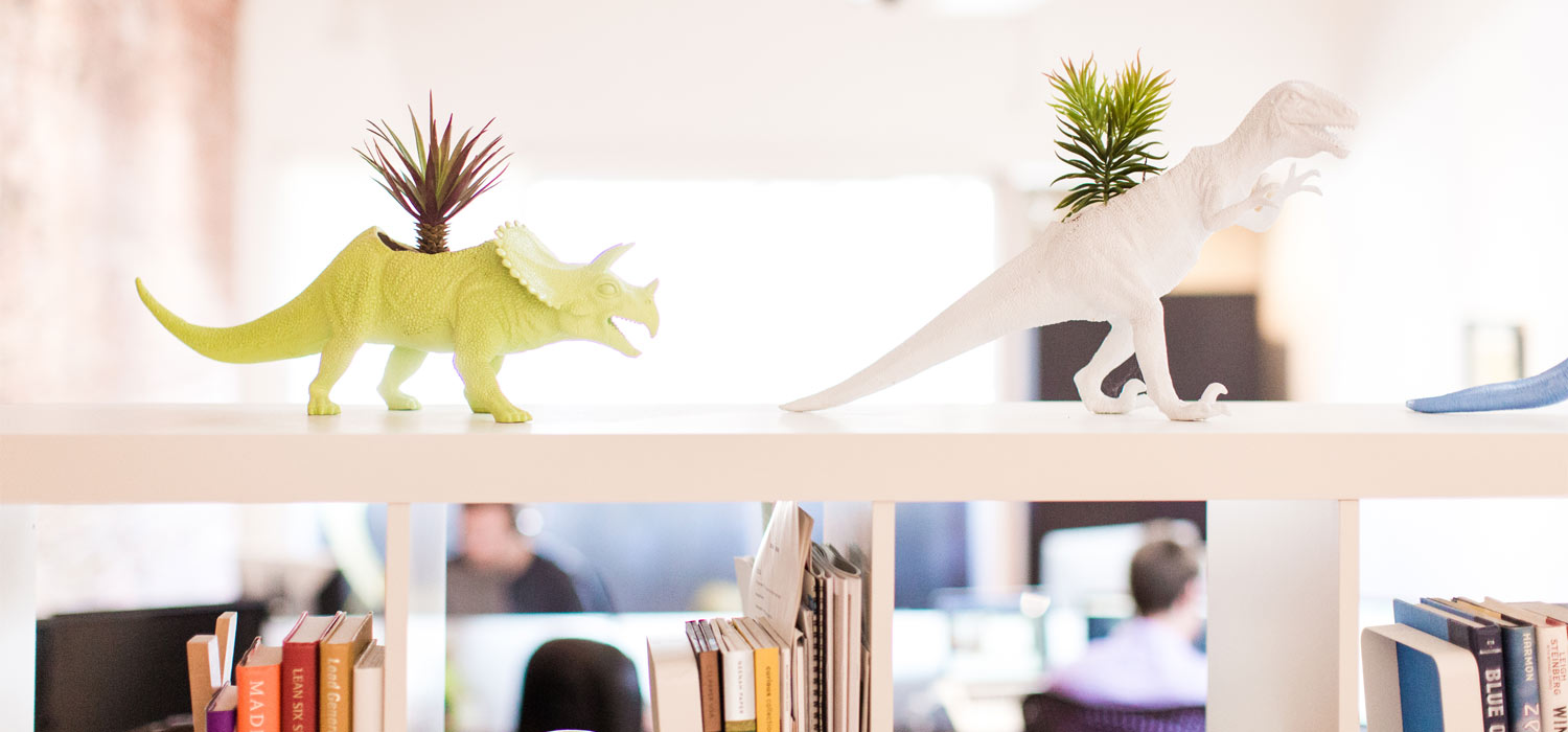 dinosaur planters on bookshelf