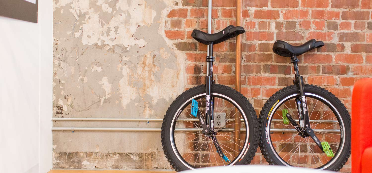 two unicycles against a brick wall