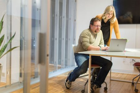 male and female employee in office with laptop
