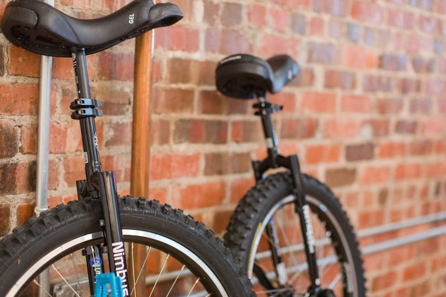 two unicycles by brick wall